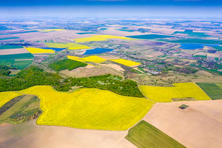 Aerial rural landscape in Romania, canola fields, forest, villages and lakes