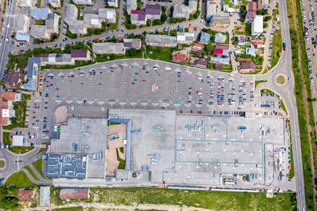 Above view of shopping mall and parking lot in residential area