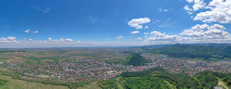 Aerial view of summer mountain city, above city view and green forest in Romania, Piatra Neamt city