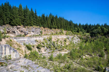 Closed travertine quarry, summer landscape of terraces in a mountain.