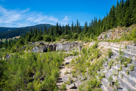 Travertine terraces in abandoned stone quarry near green forest
