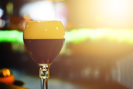 Glass of fresh dark beer on rustic pub background. The Belgian-style dubbel ranges from brown to very dark in color. They have a malty sweetness , cocoa and caramel aromas and flavors. 版權商用圖片