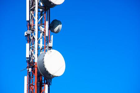 señal de la transmisión de la torre móvil de la comunicación del teléfono con el fondo del cielo azul y la antena Foto de archivo