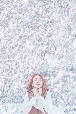 Beautiful young woman freezes in the winter suburb. Concept of warm winter clothes. Vertical portrait Banco de Imagens