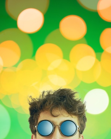 Man looks out. Person in sun glasses with disheveled hair on green background with bright yellow lights. Copy space for text. Crop 4x5 vertical