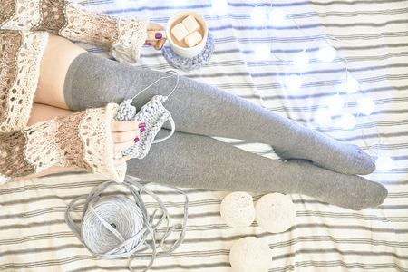Woman on the bed knits a scarf. Female feet on a bed in socks with a coffee and three marshmallows. Top view 스톡 콘텐츠