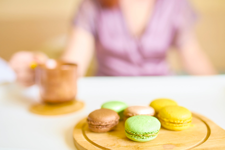 Young beautiful caucasian woman is enjoying her morning breakfast of black coffee, French macarons served on a tray. Breakfast in bed concept