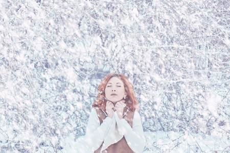 Portrait of a cute redhead in a frosty park. Photos in warm colors. Concept of warm winter clothes