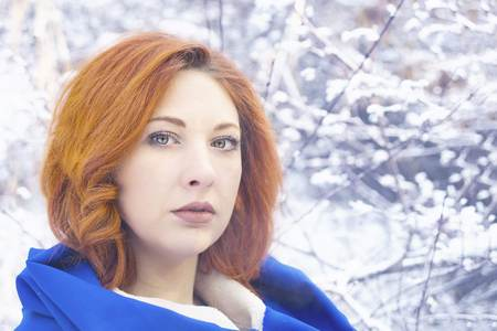 Winter portrait of a young fashionable beautiful female with red hair. Woman breathing on her hands to keep them warm at cold winter day.