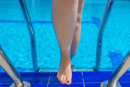 Woman swimming in the pool. Top view of female leg standing beside the edge of blue swimming pool on the sunny day.