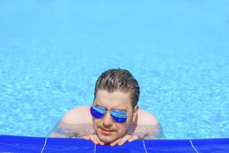 Man swimming in the pool. Man in pool having fun on summer holidays. Young man swimming and lurking on vacation. Stock Photo