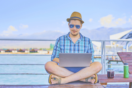 Young businessman resting on piers, enjoying summertime in resort spa near sea while working remotely at laptop computer connected to wireless internet. 스톡 콘텐츠