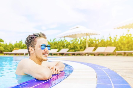 A man looks out of the pool, hanging on the railing. Close up portrait of a handsome and happy mid aged man relaxing resting on his hands at the side of a sun bathed swimming pool smiling.