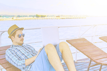 Young businessman resting on piers, enjoying summertime in resort spa near sea while working remotely at laptop computer connected to wireless internet. 版權商用圖片