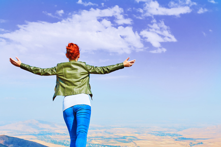 Image of a girl in a field standing in the distance with her back to the camera and her arms outspread in celebration of a beautiful sunny summer day and freedom