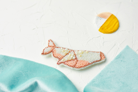 Process of creating jewelry from beads and river pearls in the form of a whale