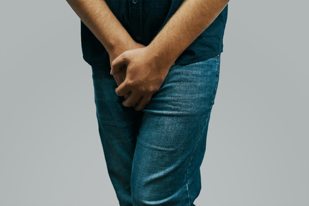 Man in a green shirt and jeans feels pain in the crotch hiding behind his hands Archivio Fotografico