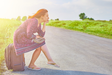 Awesome woman in summer dress and hat hitchhiking with suitcase on the road at spring. Female sitting on Luggage waiting for transport. Travel concept Stock fotó