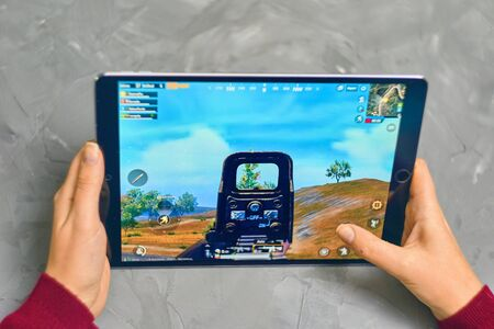 Bishkek, Kyrgyzstan - January 21, 2019: Woman playing pubg coop multiplayer battle royale game on Apple ios tablet iPad Pro