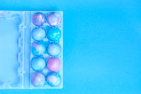 Painted Easter eggs with space intergalactic pattern in stand on blue background Stock Photo