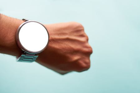 Smart watch on hand on light blue background with isolated, blank screen for mockup.