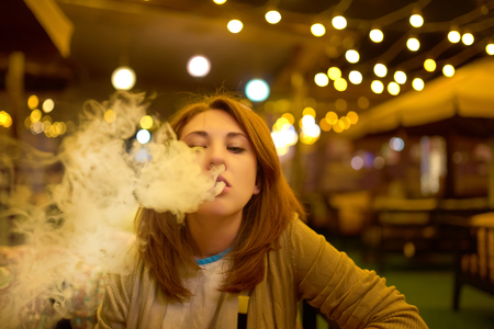 Young woman smoking hookah at the restaurant Banco de Imagens - 120200651