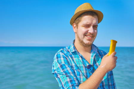Guy putting onsun protection lotion on the face. A man by the sea, his face smeared with sunscreen. Foto de archivo