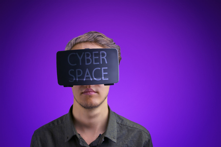 Young man in a shirt uses virtual reality glasses with the inscription
