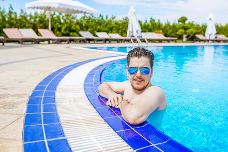 A man looks out of the pool, hanging on the railing. Close up portrait of attractive young man in sunglasses resting on edge of swimming pool. 版權商用圖片 - 128771647