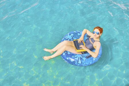 Workaholic woman working on vacation, the concept of remote work. Business woman sitting in a inflatable ring at sea and using laptop.