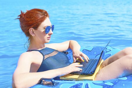 Beautiful young woman with on donuts and a desktop computer relaxing in the ocean. 版權商用圖片