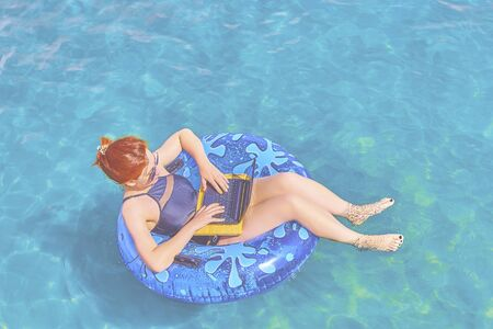 A young woman is floating on the sea in a swimming circle. A girl is relaxing on the sea on the inflatable ring with minicomputer. 版權商用圖片