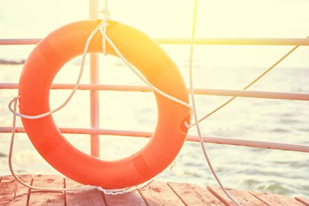 Orange lifebuoy with rope on a wooden pier near sea. Close up of lifebuoy on wooden pier at the beach. 版權商用圖片