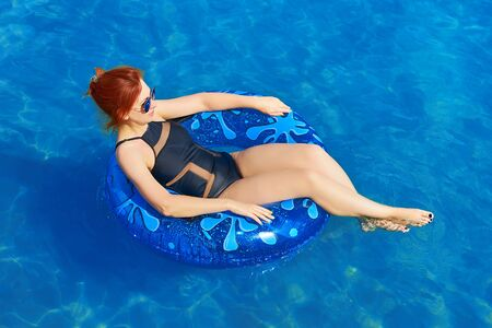 Beautiful young woman relax on inflatable ring in sea water