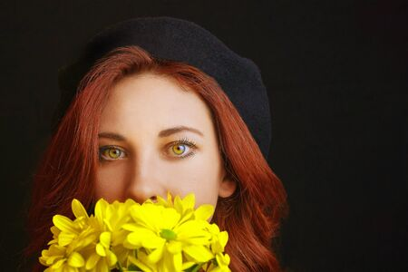 French redhead woman in black beret holds and sniffs yellow chrysanthemums
