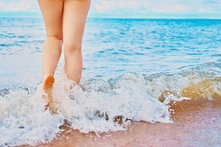In the frame of a woman's feet walking on the beach by the sea on a Sunny day in a tropical hotel on vacation. Waves of ocean wash her feet