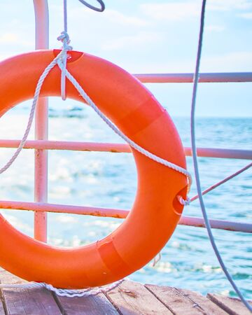 Orange lifebuoy with rope on a wooden pier near sea. Yellow ladder and an orange lifebuoy with rope on the pier in the background of the river. 版權商用圖片 - 128772104