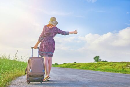 Awesome female traveler in summer dress and hat hitchhiking with big bag at spring. Beauty woman thumb up and walking on the road with Luggage. Tourist concept 스톡 콘텐츠