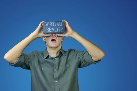 Young man in shirt enjoys and amazed by virtual reality glasses with virtual reality inscription on them in front of blue background