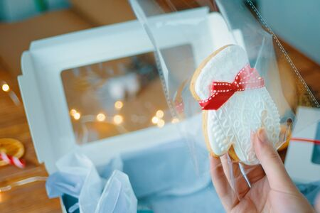 Woman prepares a Christmas cookies in the form of a white mitten in a box for gift