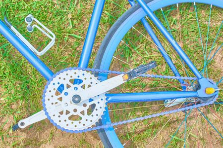 Bright blue bike lying on the grass with sand on a Sunny day Stock Photo