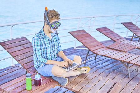 A man in an underwater mask, working on vacation. Фото со стока