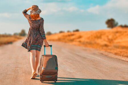 Pretty woman in summer dress and hat hitchhiking with suitcase. Girl walking on the road with Luggage at fall. Journey concept