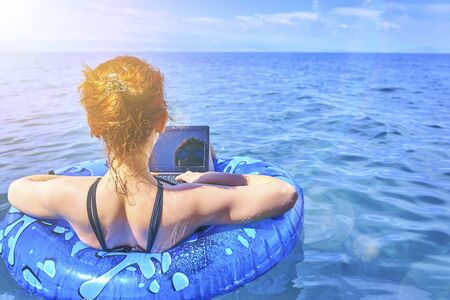 Beautiful young woman with on donuts and a desktop computer relaxing in the ocean. Imagens