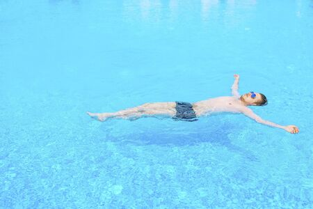 Side view of a man swimming in a pool at warm and sunny summer day. Relax conception.