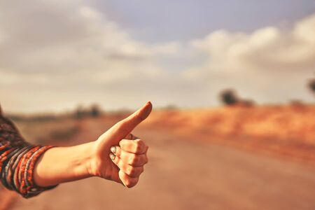 Hand of woman tourist hitchhike with thumbs up form the asphalt road go to travel at autumn