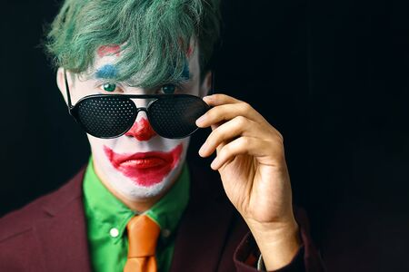 Man in mime makeup cosplay with green hair and red suit orange tie and green shirt. Clown looks through his glasses with a not bad expression