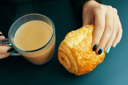 Woman having Breakfast French croissant and coffee on a dark table