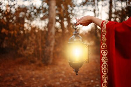 Woman holding a lantern with a candle. A woman in the woods holding a lantern with a candle.