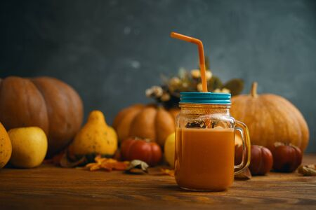 Pumpkins juice in bottles with pumpkins. Glass of fresh pumpkin smoothie on wooden background Stock Photo
